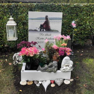 front picture of installed peaceyard gravestone, model ada in glacier white color with standard base and square planter