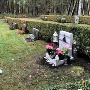 side picture of installed peaceyard gravestone, model ada in glacier white color with standard base and square planter