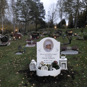 picture of installed peaceyard gravestone, model cora in glacier white with round planter