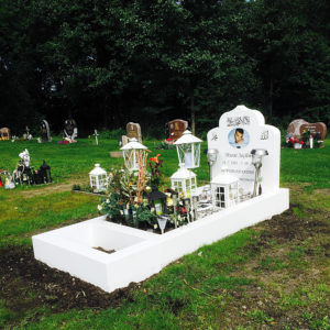 picture of installed peaceyard gravestone, custom model arwa in glacier white color with standard base, square planter and square full frame