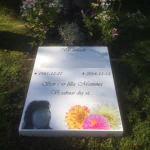 picture of installed peaceyard horizontal gravestone, model custom flora in glacier white color with customer graphics
