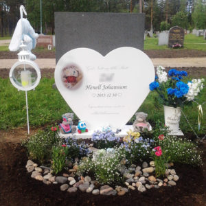 picture of installed peaceyard upright gravestone, model maida in glacier white color with customer graphics