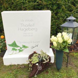 picture of installed peaceyard upright gravestone, custom model ada (shorter) in glacier white material with customer graphics and standard base