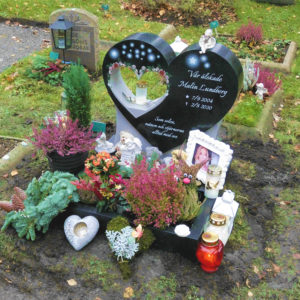 picture of installed peaceyard upright gravestone, custom model in night sky material with dove material inserts with customer graphics, integrated lantern and square planter