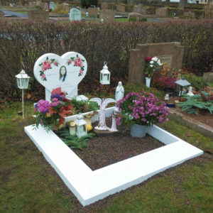 picture of installed peaceyard upright gravestone, model melody in glacier white material with customer graphics and everest square angeled frame