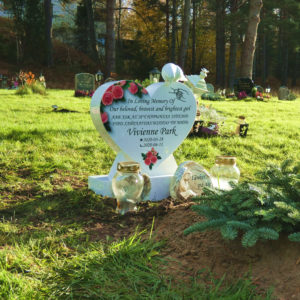 picture of installed peaceyard upright gravestone, model melody (mini) in glacier white material with customer graphics